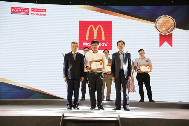 Mr. Nguyen The Nhat Toan, Marketing Director of McDonald's Vietnam (white shirt, middle) receives a certificate for McDonald's Chicken being honored in the Top 100 Trusted & Consumed products (Photo: McDonald Vietnam)