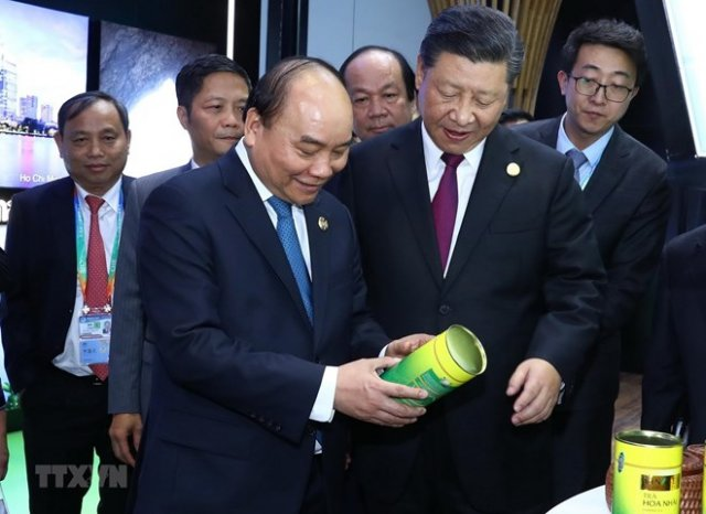 Prime Minister Nguyen Xuan Phuc  (front, left) and Party General Secretary and President of China Xi Jinping (front, right) visit the Vietnamese pavilion at the first China International Import Expo (Photo: VNA)